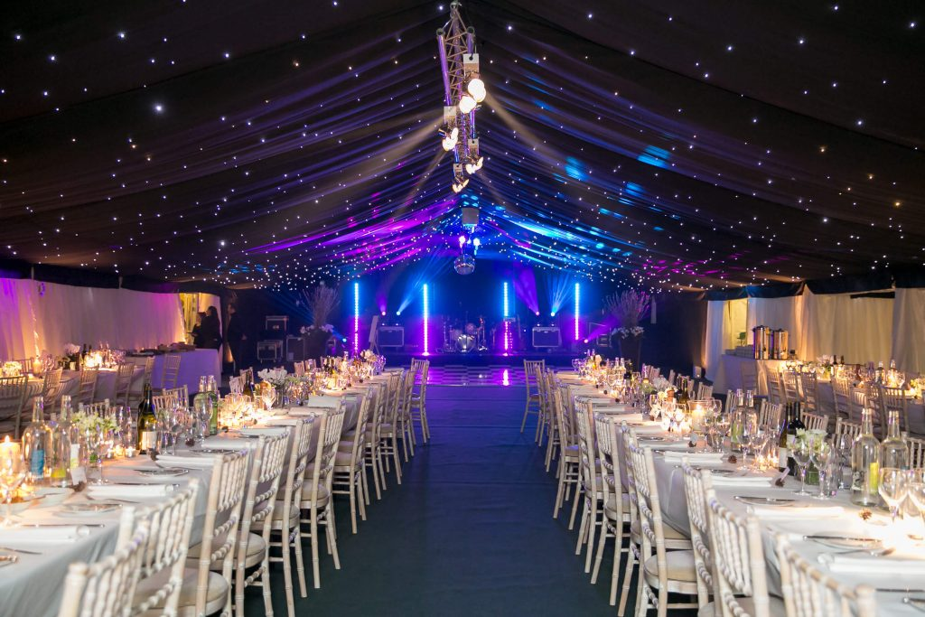 Wedding marquee with trestle tables and blue lighting.