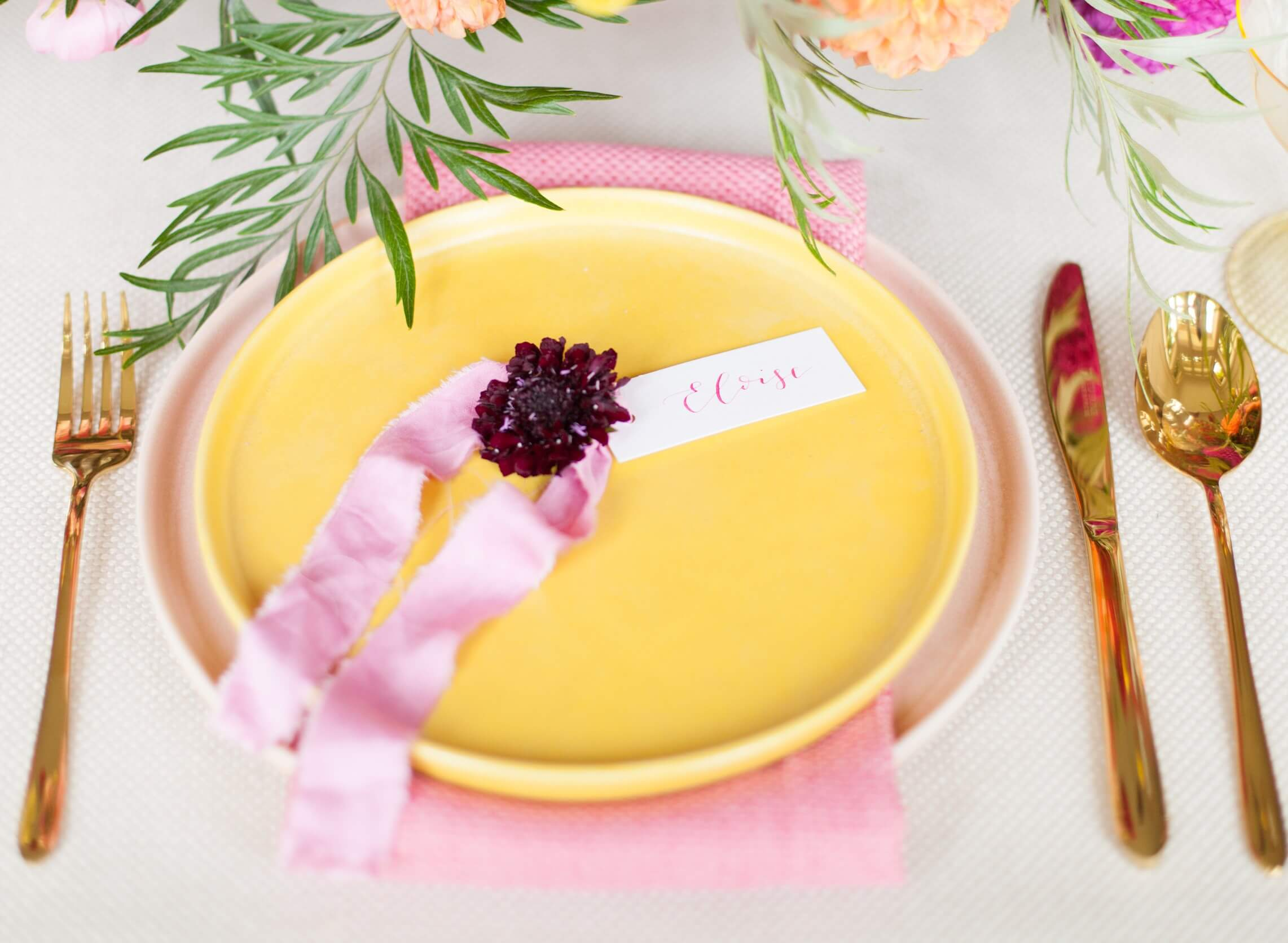 Colourful yellow plate and pink napkin with gold cutlery for marquee decoration