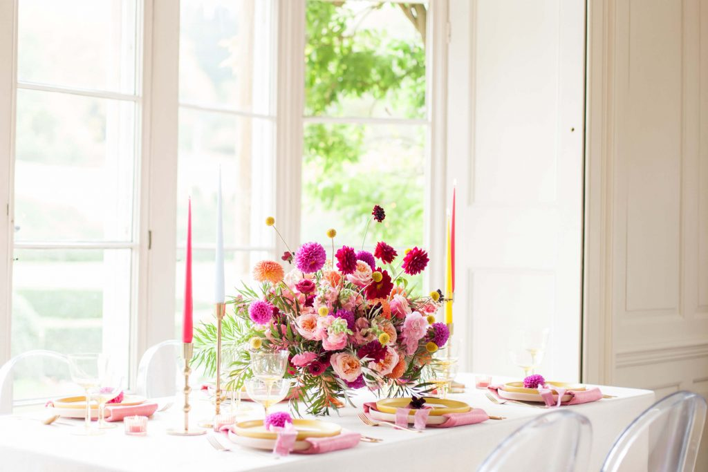Pink tall candles and pink floral centrepiece for wedding marquee decoration