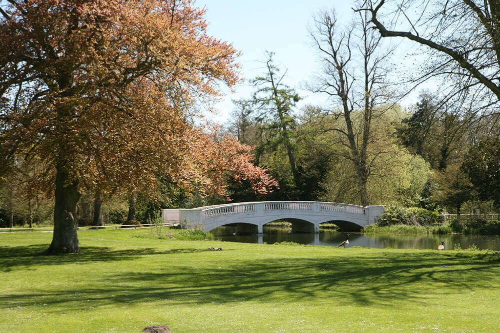 Stunning grounds with river and white bridge at Donnington Grove Hotel an impressive Berkshire Wedding Venue